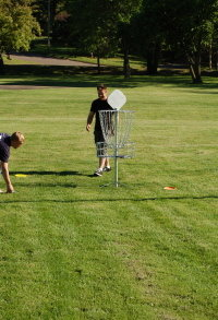 Men Close to the Basket Playing Disc Golf
