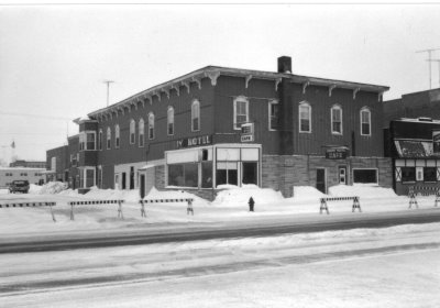 An old building with blockades to keep cars from going thru in the deep snow