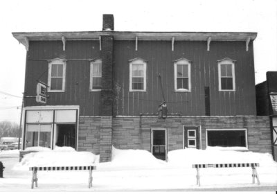 An old building with snow piles in front