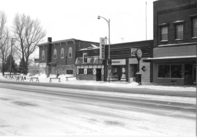 A black and white photo of a row of historical businesses