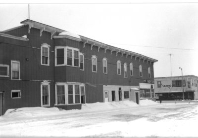 A black and white photo of a historic building after a snow storm